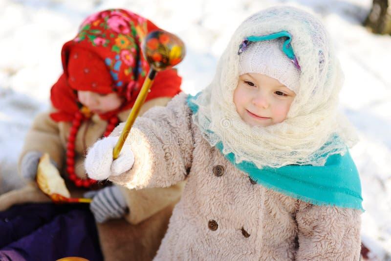 Mała dziewczynka w chustka na głowę w Rosyjskim stylu z drewnianym s, obraz royalty free