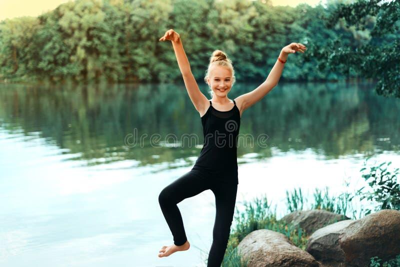 Mała dziewczynka w czarnej koszulce i leggings robi fizycznemu ćwiczeniu obraz stock