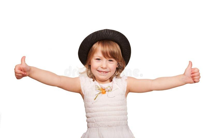 Mała dziewczynka w czarnym kapeluszu pokazuje aprobata znaka. obraz royalty free
