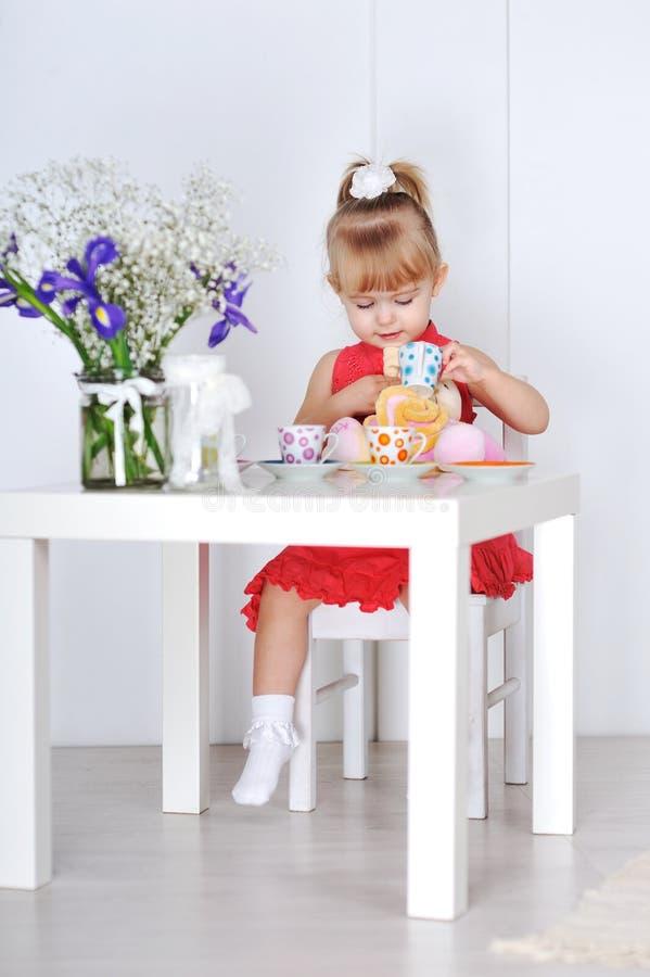 Mała dziewczynka w czerwieni sukni siedzi przy stołem i nawadnia filiżanki dol zdjęcie royalty free