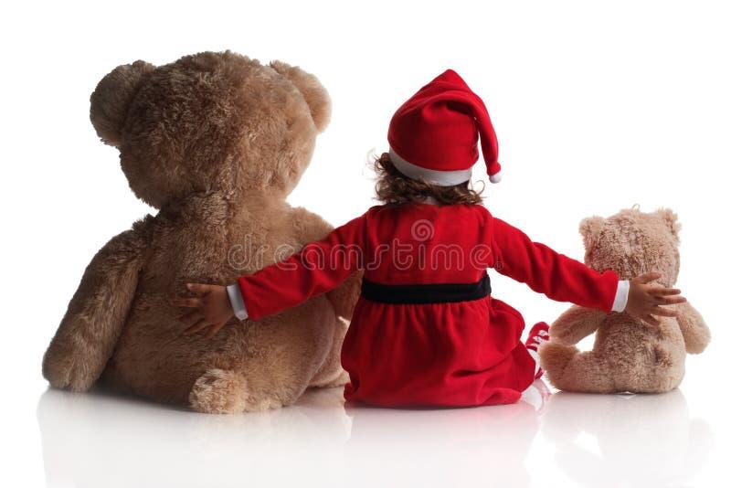 Mała dziewczynka w czerwonym Santa kapeluszu trzyma miś zabawki na białym tle zdjęcia royalty free