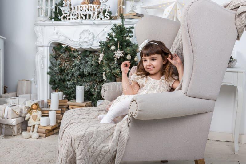 Mała dziewczynka w eleganckim świątecznym Bożenarodzeniowym wnętrzu fotografia stock