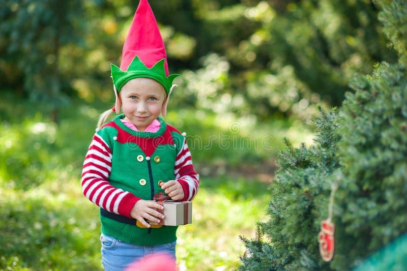 Mała dziewczynka w elfa kapeluszu i puloweru czekaniu dla boże narodzenia w drewnie Długość portret dziecko blisko bożych narodze fotografia stock