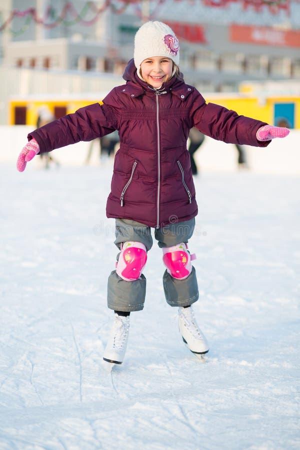 Mała dziewczynka w kolanowych ochraniaczów jeździć na łyżwach obrazy royalty free