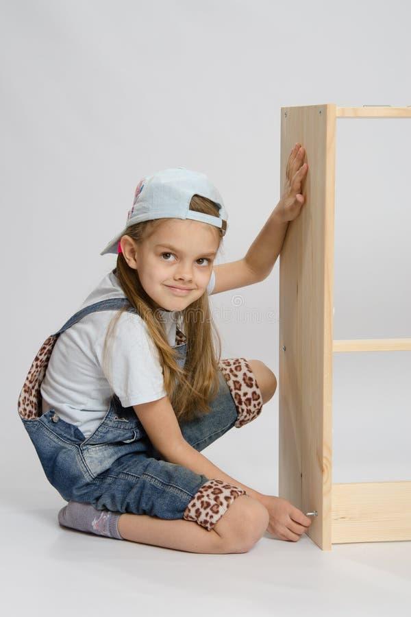Mała dziewczynka w kombinezonu poborcy meblarska zwrot śruba na dresser fotografia royalty free