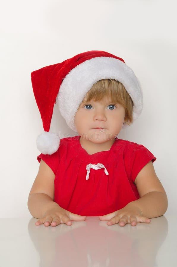 Mała dziewczynka w kostiumu Santa przy stołem obrazy royalty free