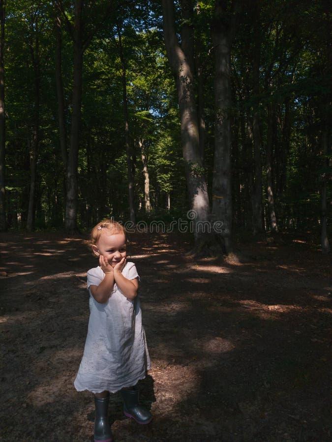 Mała dziewczynka w lasowi bawić się i ono uśmiecha się obrazy royalty free