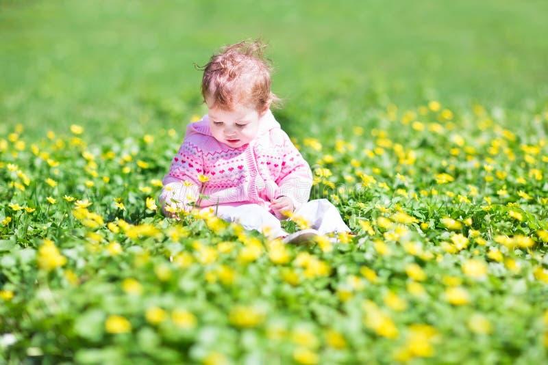 Mała dziewczynka w ogródzie z wiele żółtymi kwiatami obraz royalty free