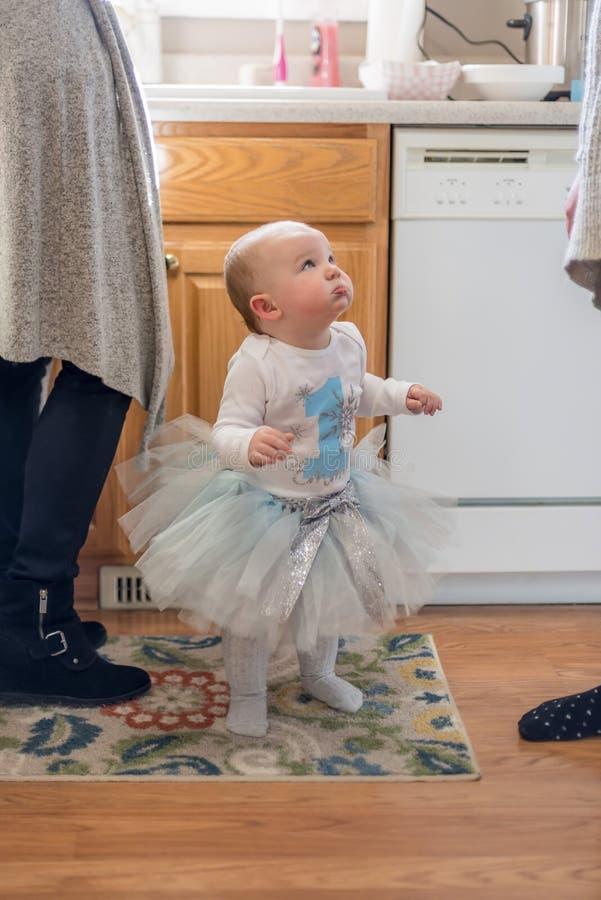 Mała dziewczynka w pierwszy urodzinowym stroju przyglądającym przy dorosłymi w zestawie up zdjęcia stock