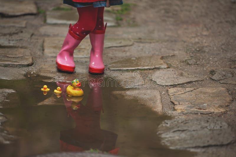 Mała dziewczynka w podeszczowych butach bawić się z żółtą gumą nurkuje w a obraz royalty free