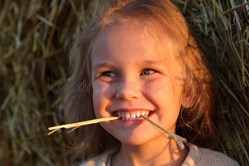 Mała dziewczynka w polu z siano rolkami przy zmierzchem obraz royalty free