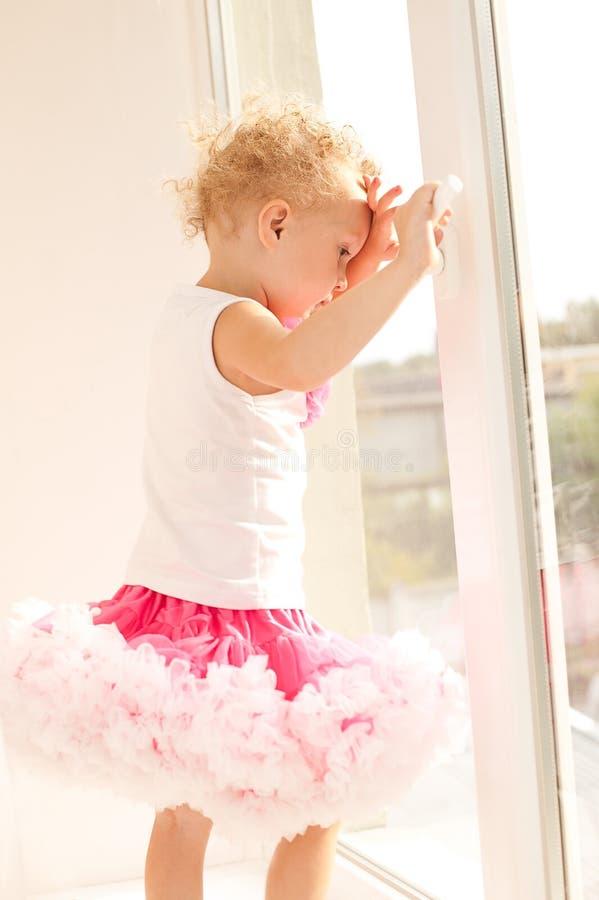 Mała dziewczynka w puszystej spódnicowej pozyci przy otwartym okno A fotografia royalty free