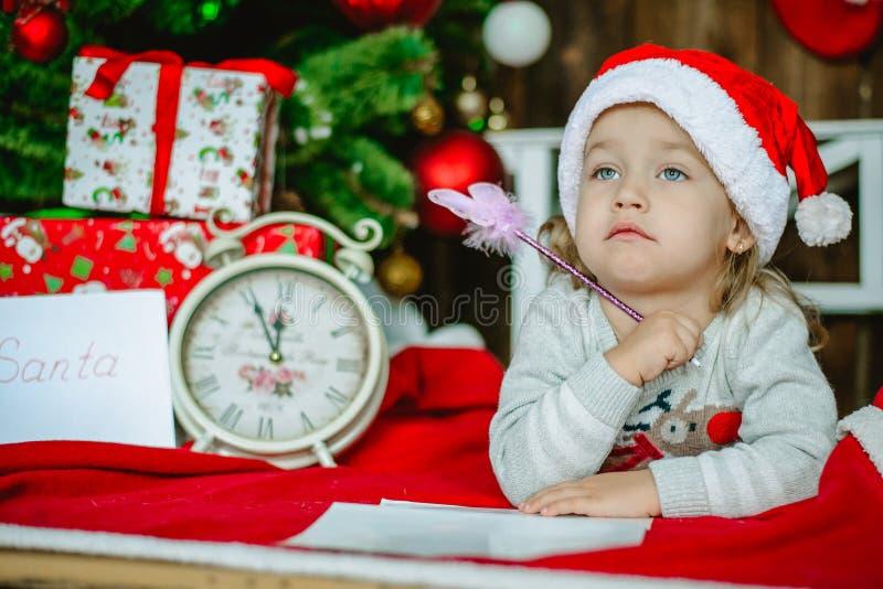 Mała dziewczynka w Santa kapeluszu pisze liście Święty Mikołaj zdjęcia royalty free