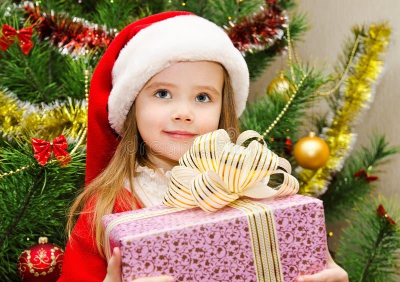 Mała dziewczynka w Santa kapeluszu z teraźniejszością boże narodzenia obraz royalty free