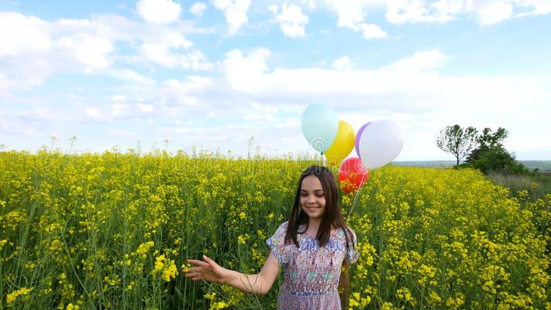 Mała dziewczynka w smokingowym bieg przez żółtego pszenicznego pola z balonami w ręce Zwolnione tempa zdjęcia stock