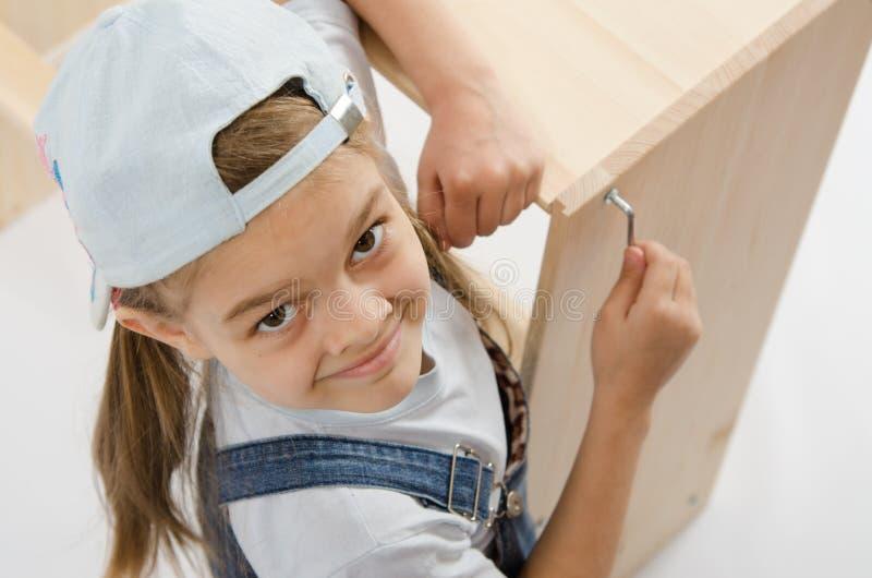Mała dziewczynka w smokingowym poborcy meble dociska śruby Allen fotografia stock