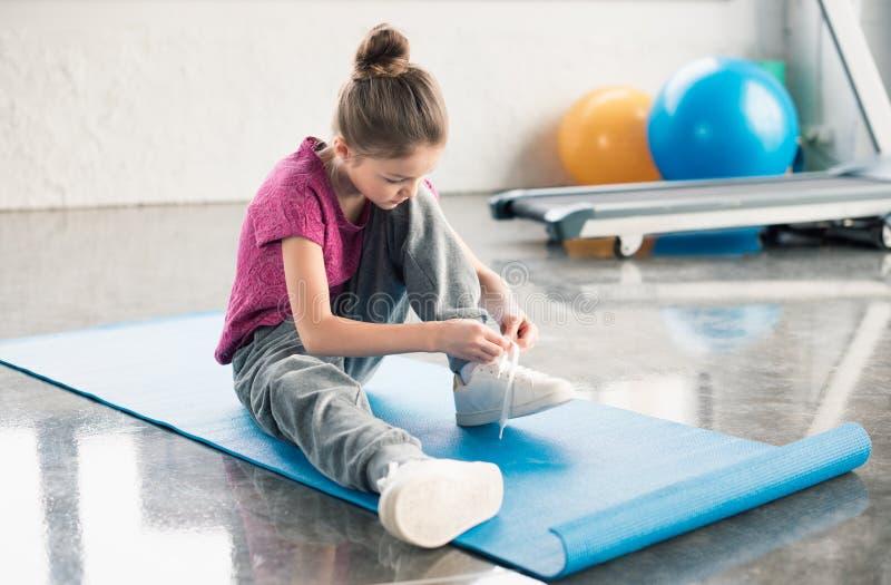 Mała dziewczynka w sportswear obsiadaniu na matowym i wiąże shoelace w gym obrazy royalty free