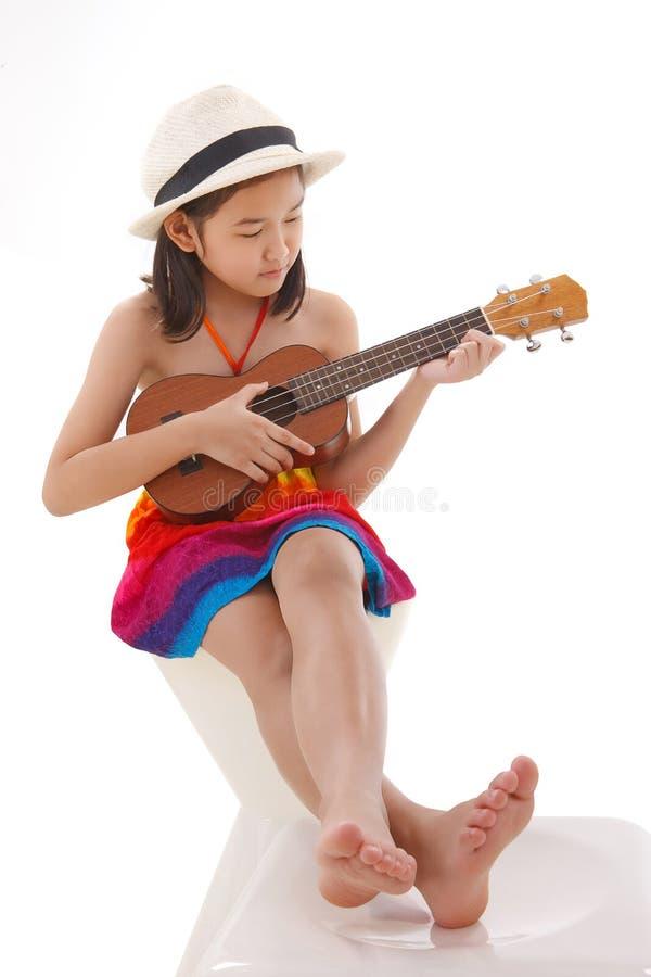 Mała dziewczynka w sukni bawić się ukulele obrazy stock