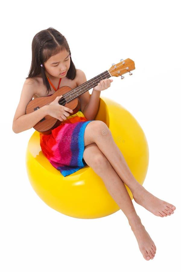 Mała dziewczynka w sukni bawić się ukulele fotografia stock