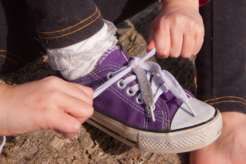 Mała dziewczynka wiąże shoelaces fotografia royalty free