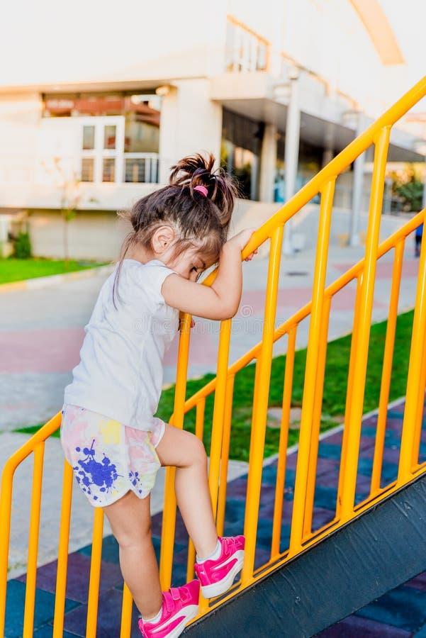 Mała dziewczynka wiąże wspinać się od kruszcowych schodków barów obraz stock