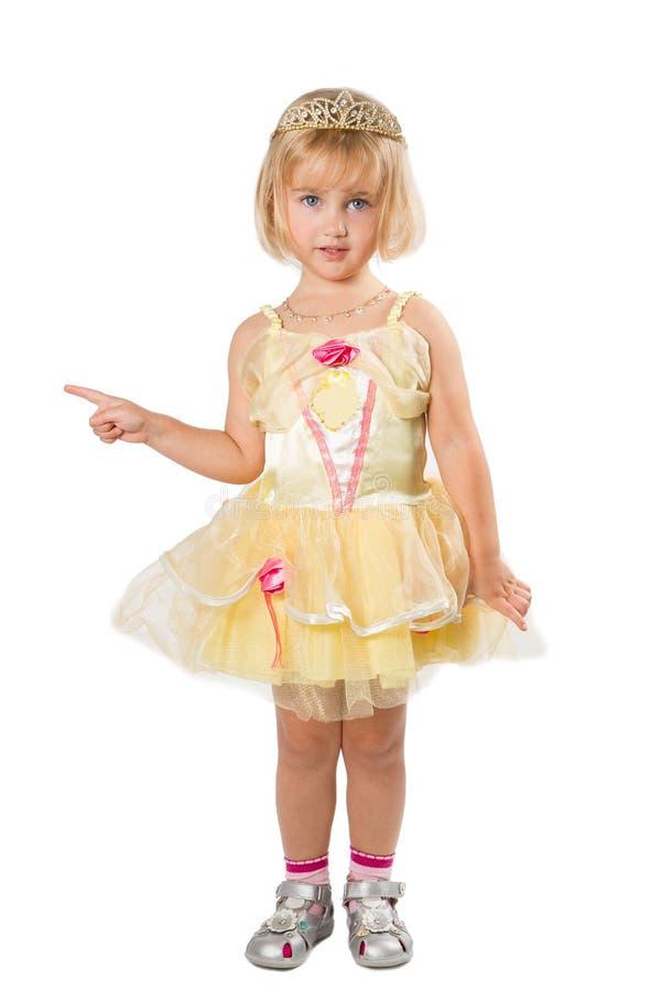 Mała dziewczynka wskazuje jego palcowego dalej w pięknej kolor żółty sukni zdjęcia royalty free