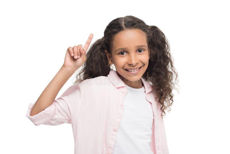 Mała dziewczynka wskazuje up z palcowym i ono uśmiecha się przy kamerą zdjęcie stock