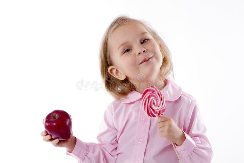 Mała dziewczynka wybór jeść lizaka lub jabłka obraz stock
