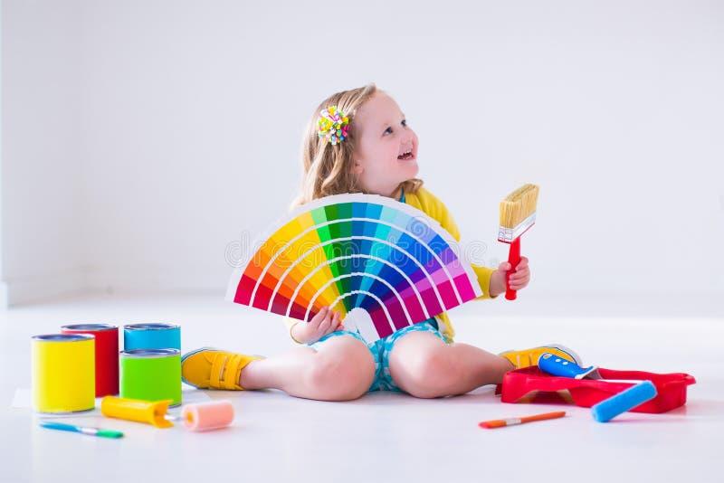 Mała dziewczynka wybiera farba kolor dla ściany zdjęcie royalty free