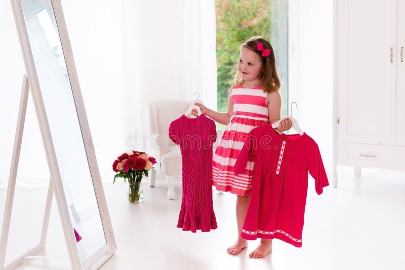 Mała dziewczynka wybiera suknie w białej sypialni obraz royalty free