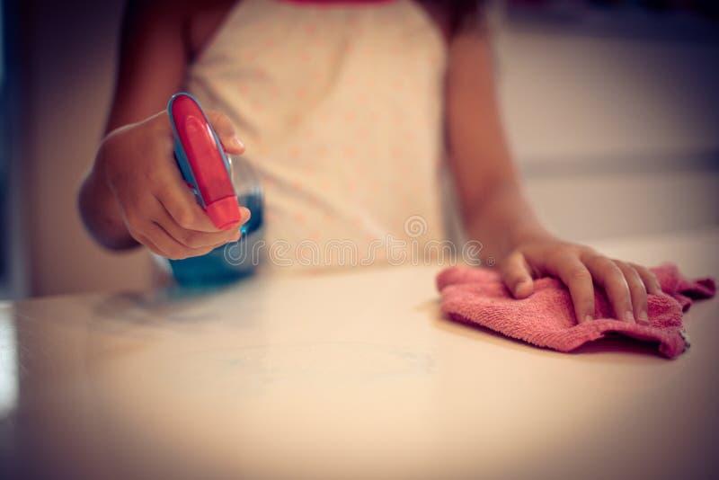 Mała dziewczynka wyciera pył na stole fotografia stock