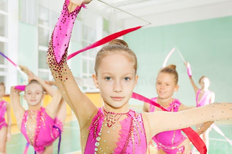 Mała dziewczynka wykonuje gimnastyczki ćwiczenie w grupie obrazy royalty free