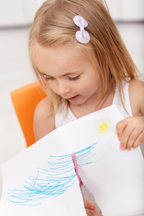 Mała dziewczynka wymagająca w ręce wykonuje ręcznie projekt - używać bezpieczeństwo s fotografia stock