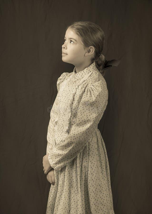 Mała dziewczynka xx wiek odzież w antykwarskiej fotografii z kolei zdjęcie royalty free