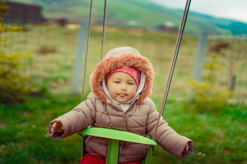 Mała dziewczynka z śmieszną twarzą na huśtawce w lato czasie fotografia stock