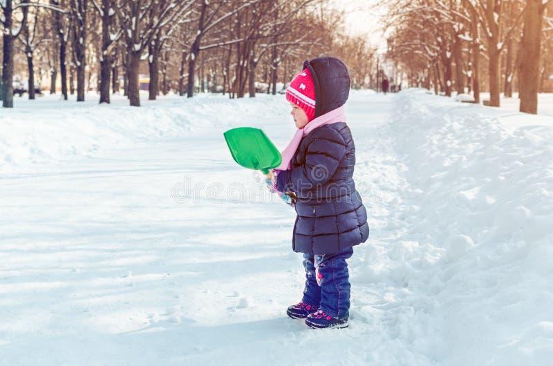 Mała dziewczynka z śnieżną łopatą bawić się outside w zimie obraz stock