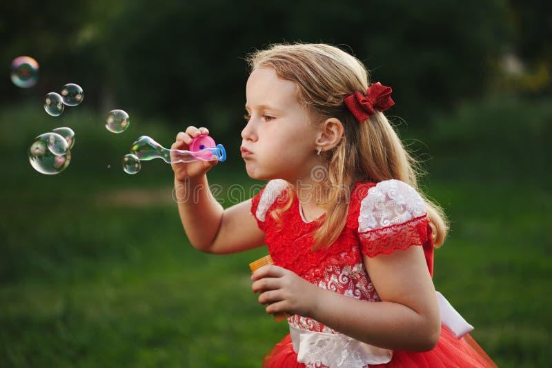 Mała dziewczynka z bąblami w lato parku zdjęcia stock