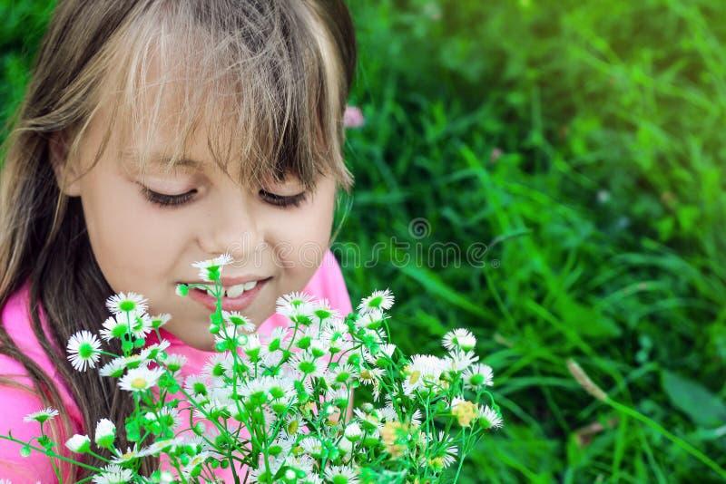 Mała dziewczynka z bieżącym włosy obwąchuje wildflowers obrazy royalty free