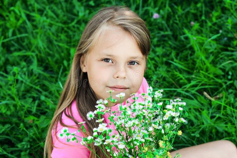 Mała dziewczynka z bieżącym włosy obwąchuje wildflowers obraz royalty free