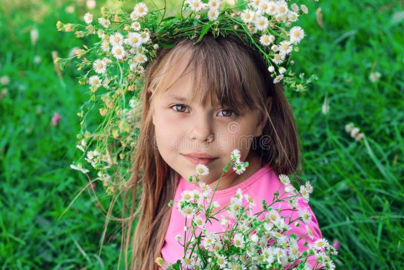 Mała dziewczynka z bieżącym włosy obwąchuje wildflowers zdjęcie stock
