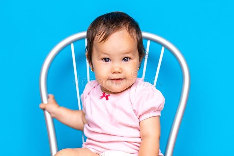 Mała dziewczynka z ciemnym włosy i brązem przygląda się mieszanego rase, kazach dziewczyny i rosjanina na błękitnym tle, obrazy stock
