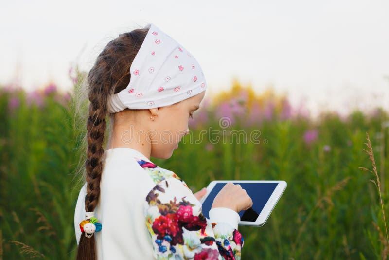 Mała dziewczynka z cyfrową pastylką na naturze fotografia stock