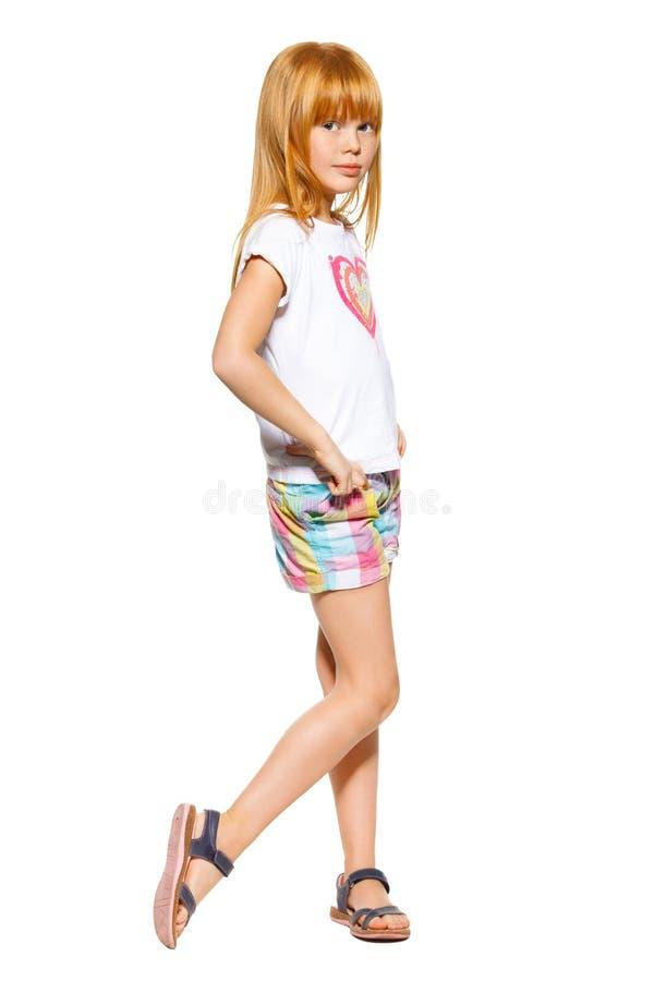 Mała dziewczynka z czerwonym włosy w skrótach i koszulce; odizolowywający na białym tle fotografia royalty free