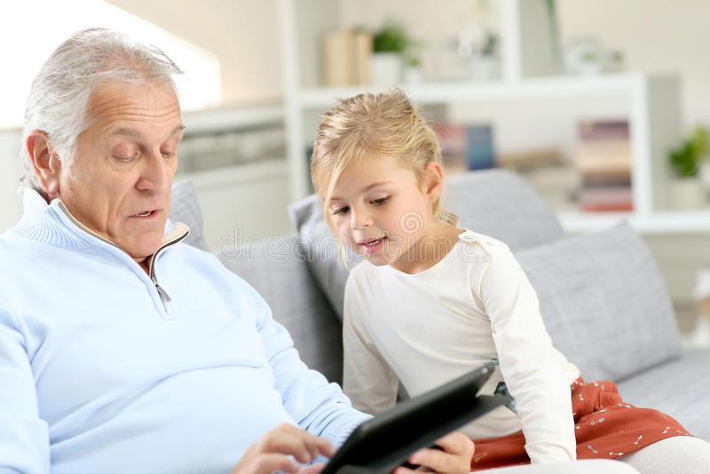 Mała dziewczynka z dziadek obsiadaniem na kanapie używać pastylkę zdjęcie royalty free