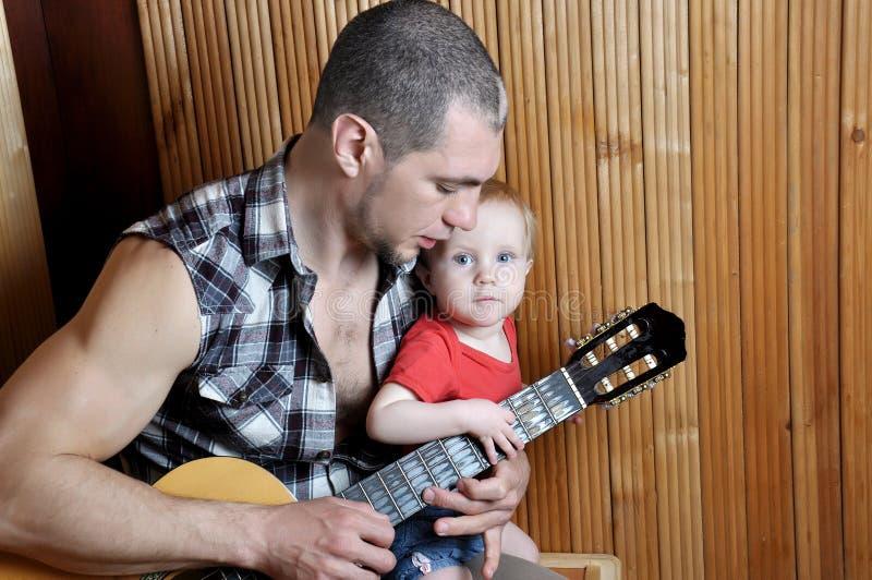 Mała dziewczynka z jego modnisia ojcem bawić się gitarę na drewnianym tle fotografia stock