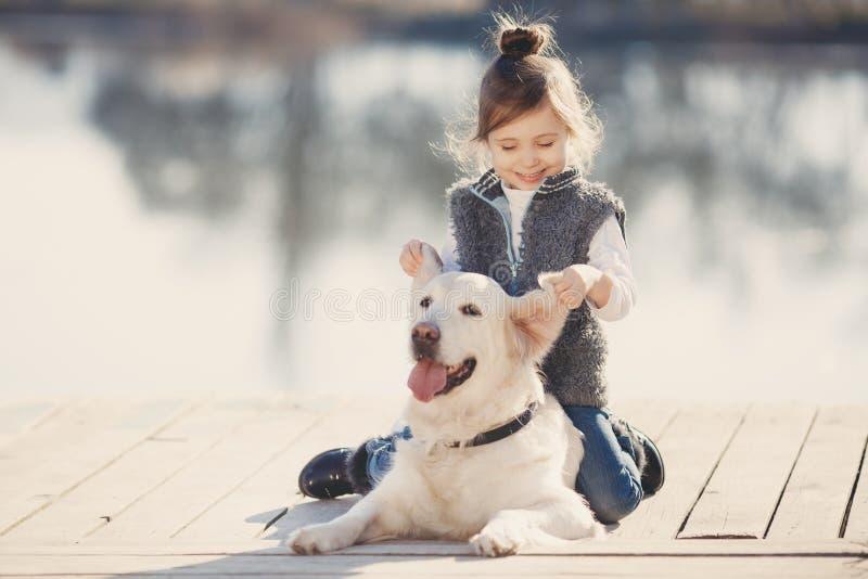 Mała dziewczynka z jego ukochanym psem przy jeziorem zdjęcia stock