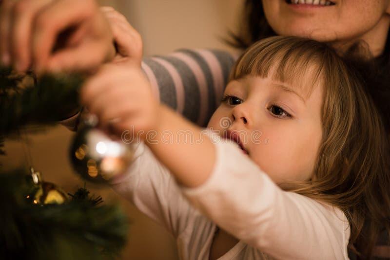 Mała dziewczynka z jej macierzystym dekoruje xmas drzewem obraz royalty free