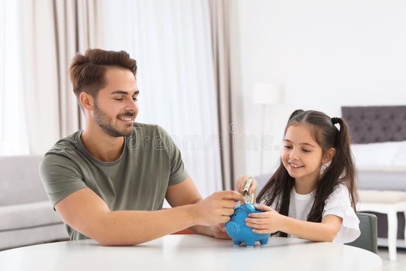 Mała dziewczynka z jej ojca kładzenia pieniądze w prosiątko banka zdjęcie royalty free