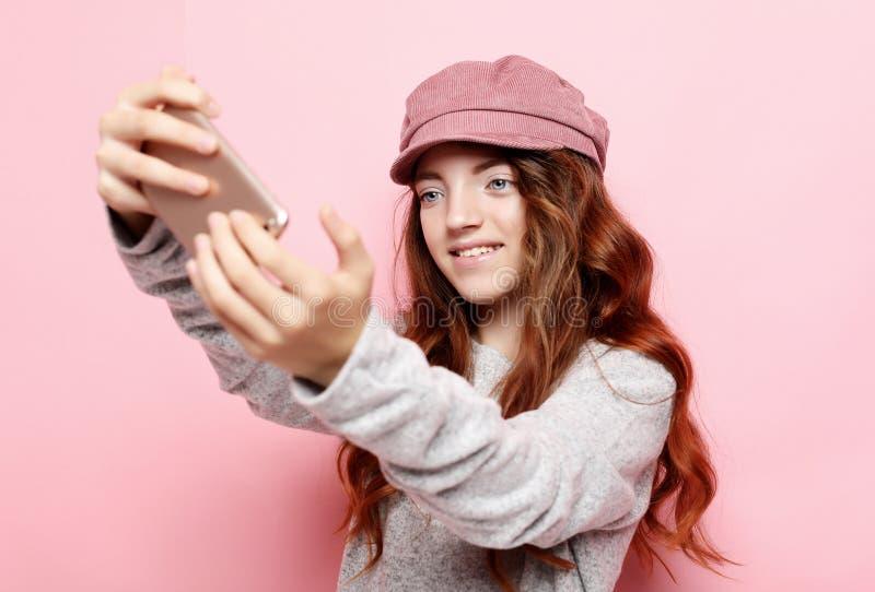 Mała dziewczynka z kędzierzawym włosy l bierze selfie nad różowym tłem zdjęcia stock
