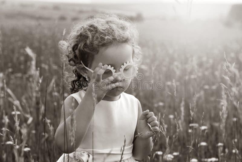 Mała dziewczynka z kędziorami w różowych szkłach w polu przy zmierzchem Dziecko w naturze zdjęcia stock